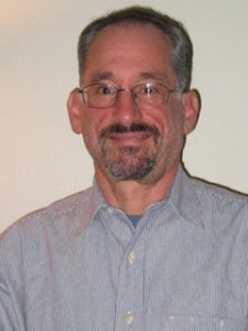 Headshot of Dan facing the camera. He is wearing glasses and a blue collared shirt. He is in front of a white wall.