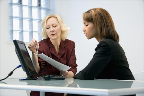 Two internal auditors review a report.